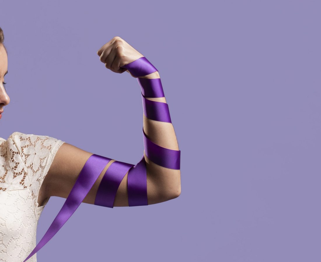 woman-flexing-her-arm-with-ribbon-and-copy-space-scaled.jpg